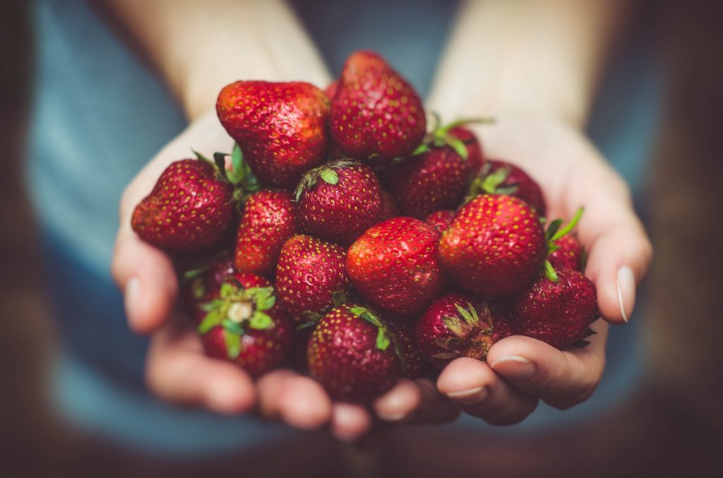 Person holding strawberries in their hand
