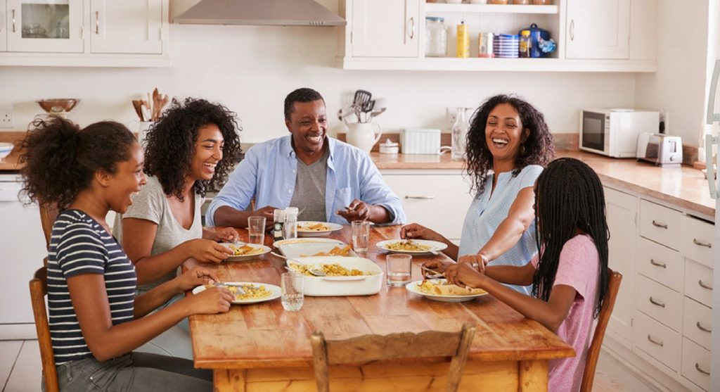 Family of five laughing around the dinner table